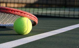 Tennis Ball & Racket on a Green Outdoor Court