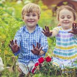 Happy little girl and boy in garden