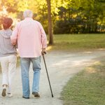 senior woman and caregiver go walking outdoors