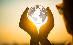 young woman at sunset holding planet earth in her hands