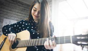 Young girl  practicing guitar.