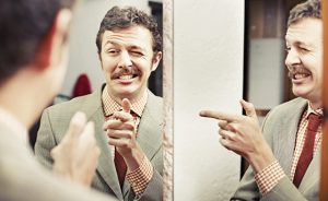 Man looking at reflection in mirror