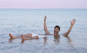 Handsome tourist man floating in Dead Sea.