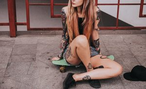 Beautiful tattooed girl with skateboard