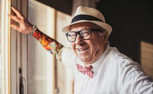 Senior man with tattoo smiling and looking at camera