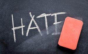 erasing hate, hand written word on blackboard being erased concept