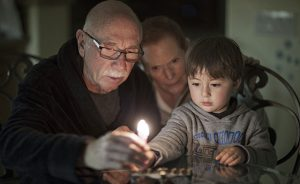 Jewish Family lighting Hanukkah Candles in a menorah for the holidays