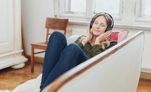 Smiling woman relaxing on sofa with headpnones