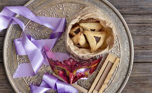 Jewish purim Hamantaschen homemade biscuits or cookies with purim mask and purim gragger