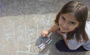 Girl kid thinking, writing and counting on mathematical equations with colored chalks on a pavement. School and vacation concept. Education concept.